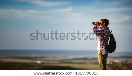 Guy looking at binoculars in hill. man in t-shirt with backpack. Young Caucasian man during hike in valley landscape Royalty-Free Stock Photo #1813990313