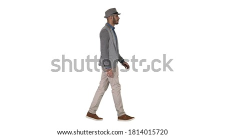 Casual arabic man in hat walking on white background.