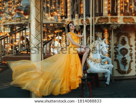 Young beautiful stylish woman sits astride a toy horse, rides a carousel. Long bright yellow dress fluttering in motion Royalty-Free Stock Photo #1814088833