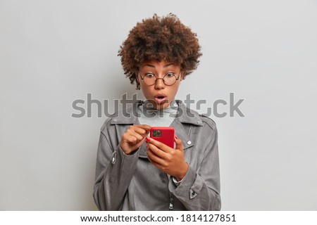 Indoor shot of impressed Afro American woman stares at mobile phone screen, keeps mouth opened. Female makes shopping online, astonished by high price wears grey jacket reads social media information Royalty-Free Stock Photo #1814127851