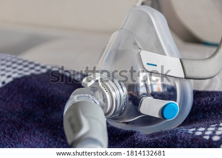 CPAP mask against obstructive sleep apnea on pillow helps patients as respirator mask and headgear clip for breathing medication with a cpap machine against snoring and sleep disorder to breath easier Royalty-Free Stock Photo #1814132681