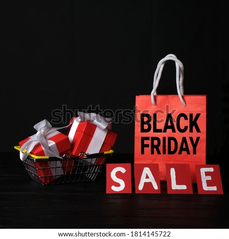 Red paper bag with the words Black Friday, gift boxes with bows in the shopping basket and the inscription SALE. Square banner on a black background with space for text. Sale concept.