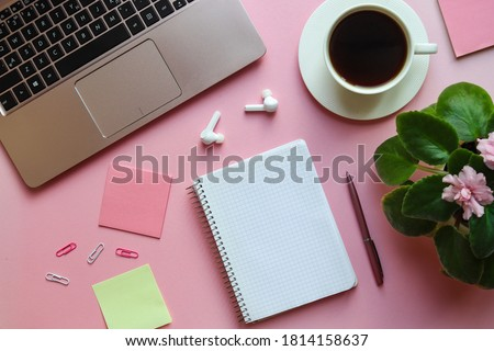Girly workspace with laptop, pink violet plant, coffee, pen, wireless headphones, open notebook and blank sheet on pink background. Girly stuff, cute working space. Top view, flat lay.