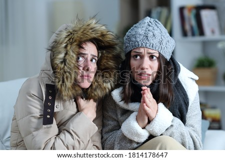 Two roommates shivering in a cold winter day on a couch in the living room at home  Royalty-Free Stock Photo #1814178647