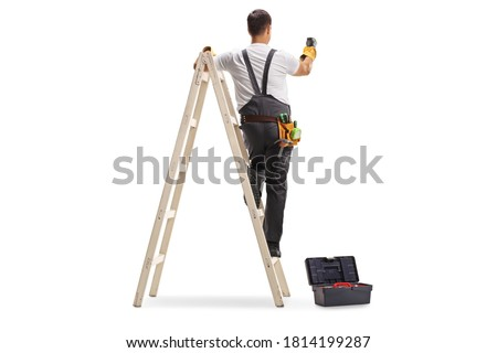 Full length rear view shot of a repairman on a ladder drilling with a machine into a wall isolated on white background Royalty-Free Stock Photo #1814199287