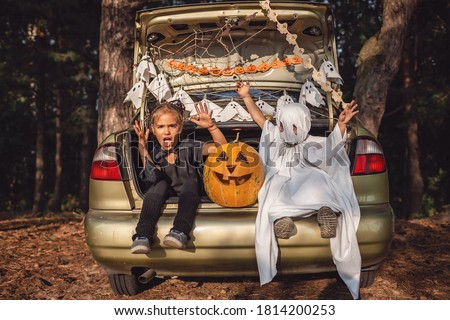 Alternative safe celebration. Cute kids preparing Halloween party in the trunk of car with carved pumpkin, spider net, ghosts and other decoration for Halloween, autumn outdoor. Royalty-Free Stock Photo #1814200253