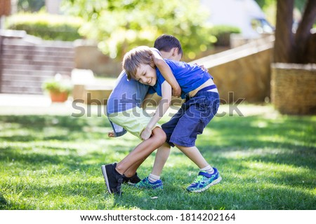 Two boys fighting outdoors. Siblings or friends wrestling on grass in summer park. Siblings rivalry.