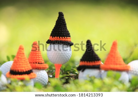 Golf ball on tee with halloween' hat for holiday season concept of golf course background