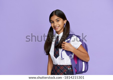 Happy smiling indian preteen girl, latin kid schoolgirl with ponytails wears uniform holding backpack standing isolated on lilac violet background looking at camera, back to school concept, portrait. #1814215301