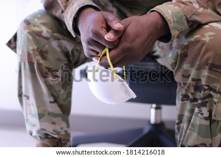Black military doctor's hands holding a white surgical mask Royalty-Free Stock Photo #1814216018