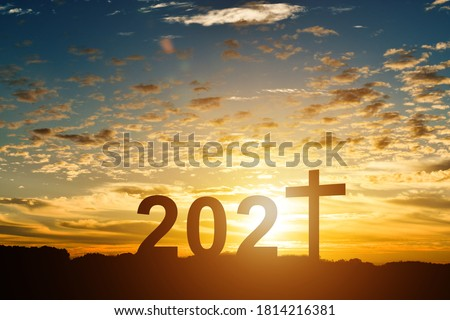 Silhouette of Christian cross with 2021 years at sunset background. Royalty-Free Stock Photo #1814216381