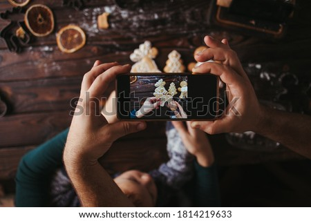 Christmas celebration mood. Man and child hands taking photography of gingerbread cookies on table with phone. Smartphone photo for social networks post. Family blog