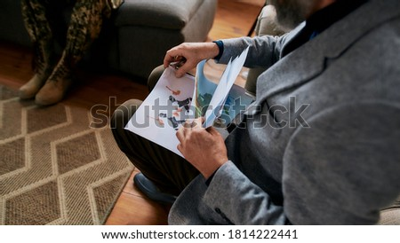 Mature psychologist choosing picture with ink stain, Rorschach Inkblot during therapy session with military man. Soldier suffering from depression. PTSD concept. Focus on picture. Web Banner