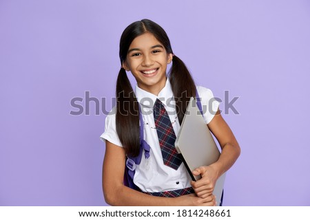 Happy smiling indian preteen girl, latin kid wears school uniform holding backpack and laptop computer isolated on lilac violet background looking at camera, remote learning online concept, portrait. Royalty-Free Stock Photo #1814248661