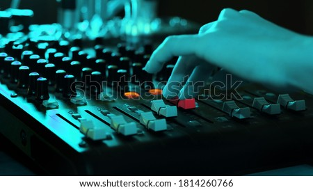 Sound engineer moving sliders In music festival concert close up. Sound designer used audio mixer in studio. DJ slider sound music to put more volume during press bottom mixer bottom on desk. Royalty-Free Stock Photo #1814260766