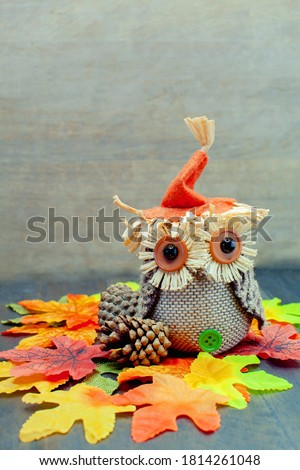 Cute craft Owl (Thanksgiving and Halloween theme) for autumn decorations with maple leaves on a wooden background.