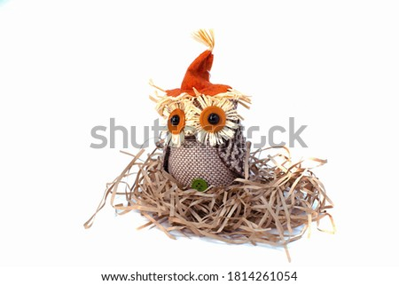 Cute craft Owl in the nest for Thanksgiving and Halloween theme. Autumn decorations on white isolated background.