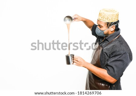 """A picture of men preparing famous Malaysia drink call """"teh tarik"""" on copyspace white background. Sweet milk tea been pull for mix well and create foam that is famous in Malaysia and South Asia region."""