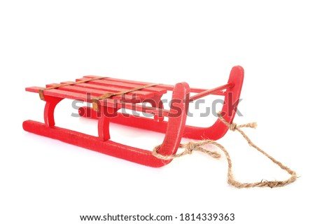 red sledge in front of white background