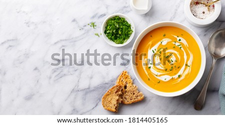 Pumpkin traditional soup with creamy silky texture. Marble background. Copy space. Top view. Royalty-Free Stock Photo #1814405165
