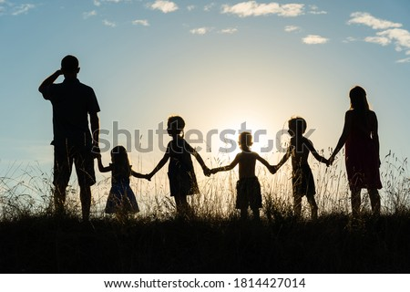Silhouette of a happy large family at sunset. Royalty-Free Stock Photo #1814427014