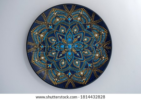 Decorative ceramic plate with black, blue and golden colors, painted plate on white background, closeup, top view. Decorative porcelain plate painted with acrylic paints, handwork, dot painting Royalty-Free Stock Photo #1814432828