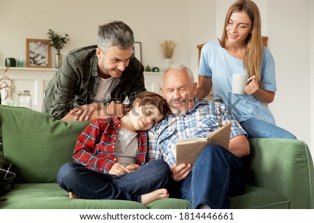 Grandfather enjoying literature together grandson and his young parents at cozy living room. Elderly man reading book aloud to cute schoolboy and his smiling family. Multi-generational family weekend Royalty-Free Stock Photo #1814446661