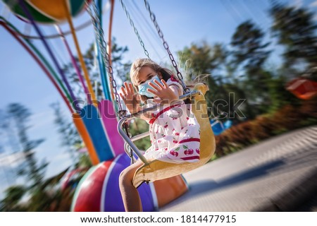 Cute school girl wearing facial mask having fun at an amusement park, new reality during covid quarantine, happy anyway, outdoor summertime Royalty-Free Stock Photo #1814477915