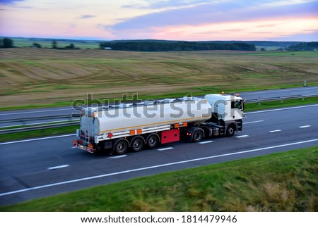 Isothermal Tank truck driving on highway. Oil and Gas Transportation and Logistics. Metal chrome cistern tanker with petrochemicals products. Liquid Chemical Freight. Soft focus possible granularity Royalty-Free Stock Photo #1814479946