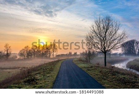 Rural country road in autumn morning sunrise. Rural road in morning sunrise. Early morning rural road sunrise landscape. Road in early morning sunrise #1814491088