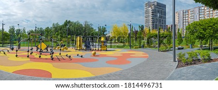 Panoramic of colorful large playground in city park. Empty modern outdoor playground in springtime. Beautiful urban place for kids games and sport Royalty-Free Stock Photo #1814496731