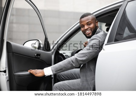 Cheerful black man in expensive suit getting in luxury car, holding door and smiling at camera. African american successful entrepreneur going to office in the morning Royalty-Free Stock Photo #1814497898