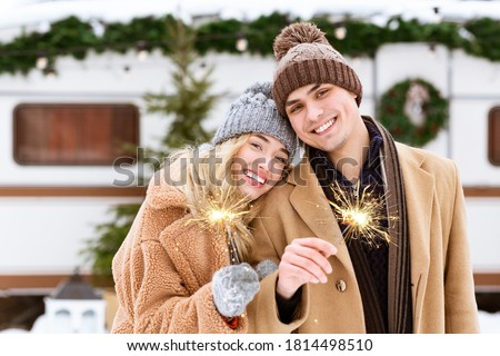 Smiling Romantic Couple In Knitted Hats Posing With Sparklers At Winter Camping, Holding Bengal Lights In Hands And Looking To Camera, Celebrating Christmas Holidays Together At Campsite, Copy Space #1814498510