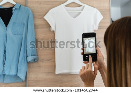 Woman taking picture of used clothes. Selling used clothes concept.