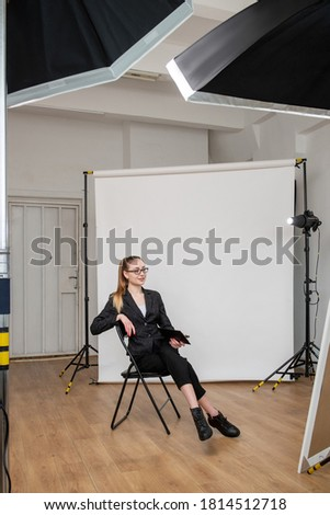 Business vlog. Shooting backstage. Creative woman posing sitting in modern studio with light equipment white backdrop. Professional photography.