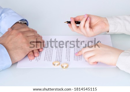 Hands of wife, husband signing decree of divorce, dissolution, canceling marriage, legal separation documents, filing divorce papers or premarital agreement prepared by lawyer. Wedding ring #1814545115