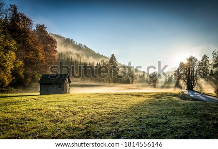 Autumn forest hut in sunrise morning fog. Sunrise fog in autumn mountains. Sunrise fog in morning #1814556146