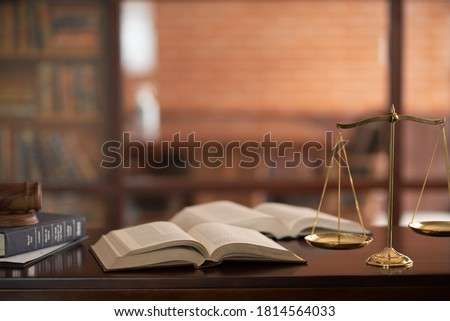 law books and scales of justice on desk in library of law firm. jurisprudence legal education concept. #1814564033