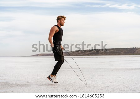 Image of caucasian athletic sportsman working out with jumping rope on nature Royalty-Free Stock Photo #1814605253
