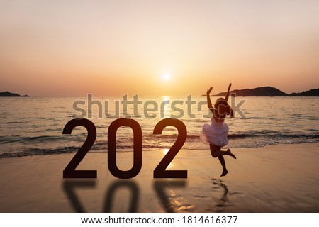 Young woman traveler jumping at the beach celebrating New Year 2021 at sunset #1814616377