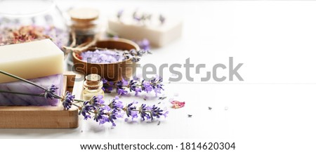 Lavender Spa products on a white table. Handmade soap on wooden soap dish, essential oil and lavender bath salt - beauty treatment. Royalty-Free Stock Photo #1814620304