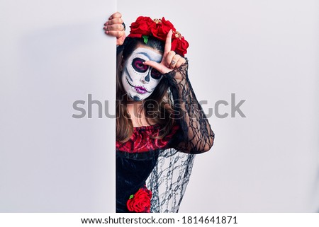Young woman wearing day of the dead custome holding blank empty banner making fun of people with fingers on forehead doing loser gesture mocking and insulting.