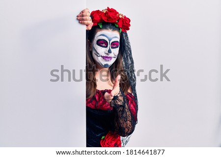 Young woman wearing day of the dead custome holding blank empty banner pointing fingers to camera with happy and funny face. good energy and vibes.