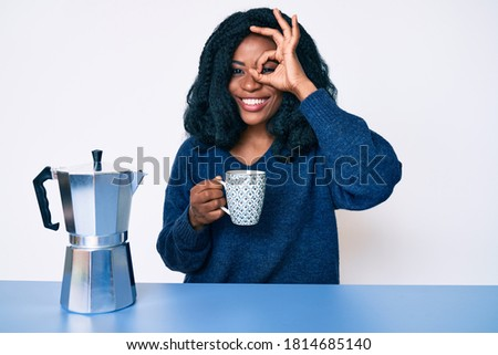 Beautiful african woman drinking a coffee from italian coffee maker smiling happy doing ok sign with hand on eye looking through fingers