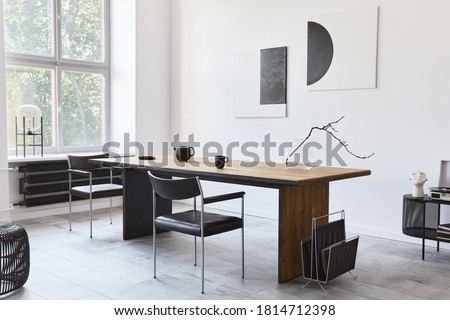 Stylish dining room interior with design wooden family table, black chairs, teapot with mug, mock up art paintings on the wall and elegant accessories in modern home decor. Template. Royalty-Free Stock Photo #1814712398