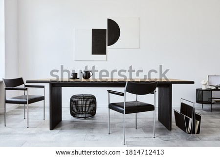 Stylish dining room interior with design wooden family table, black chairs, teapot with mug, mock up art paintings on the wall and elegant accessories in modern home decor. Template. Royalty-Free Stock Photo #1814712413