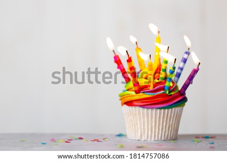 Birthday cupcake with rainbow frosting and colorful birthday candles Royalty-Free Stock Photo #1814757086