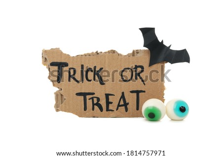Carton with text Trick or treat, bat and eye isolated on white background
