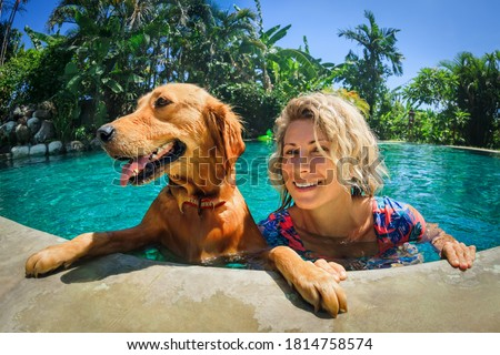 Funny portrait of smiling woman relaxing with golden retriever puppy in tropical swimming pool. Popular dog breeds, outdoor activity and fun games with family pet on summer family holiday.