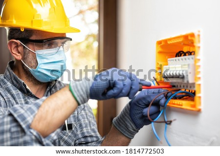 Electrician at work on an electrical panel protected by helmet, safety goggles and gloves; wear the surgical mask to prevent the spread of Coronavirus. Construction industry. Covid 19 Prevention. #1814772503